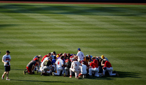 Teams pray. Reuters: Joshua Roberts